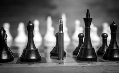 Black and white closeup shot of bullet in row of chess pieces Stock Photos