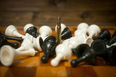 Riffle bullet on chessboard among lying chess pieces. Concept of military pow - stock photo