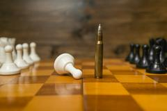 Riffle bullet on chessboard. Concept of power of guns Stock Photos