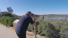 Man Views Newport Beach Back Bay Through Binoculars Stock Footage