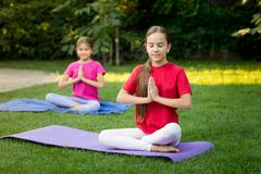 Two smiling sisters practicing yoga on grass at park - stock photo