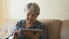 Old woman looks at pictures using a digital tablet Stock Footage