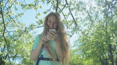Young red-haired girl in the apple orchard looking at the phone - stock footage