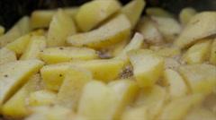 Potatos cooking on a black frying pan - stock footage