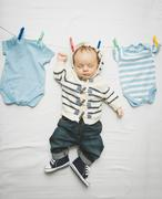 little baby boy in jeans hanging on cord next to drying clothes - stock photo