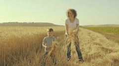 Mother And Son Trowing Ears Of Wheat Stock Footage