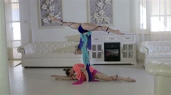 Two beautiful women perform acrobatic - stock footage