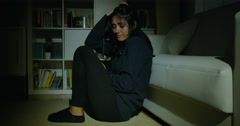 Sad woman feeling lonely at night sitting on floor almost crying dolly shot Stock Footage