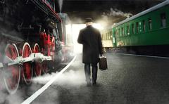 Rear view of man in bowler hat with suitcase walking on the platform next to  - stock photo