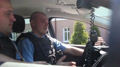 Two police in the car talking on the radio Stock Footage
