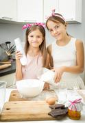 Two sister mixing ingredients for dough in big bowl on kitchen Stock Photos