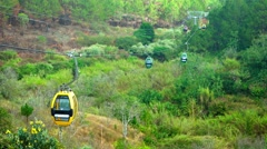 Cable cars carry passengers over wilderness, far below, near Datanla Waterfal - stock footage