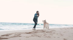 Young attractive girl playing with siberian husky dog on the beach, slow motion - stock footage