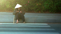 Disabled, homeless person sits on a curb along a city street in Dalat, Vietna Stock Footage