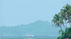 Airliner comes in for a landing at Phuket International Airport in Thailand - stock footage