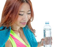 Attractive Asian woman with water bottle and towel after exercise - stock photo
