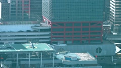 Passengers boarding an idling helicopter on an urban helipad in Hong Kong Stock Footage