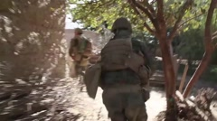 War in Afghanistan - U.S. soldiers running into position behind wall to attack - stock footage