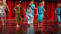 Children of tourists perform a Laotian folk dance using streamers in Laos Stock Footage