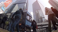 Low angle shot of heavy pedestrian traffic through intersection in Hong Kong Stock Footage