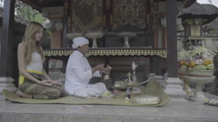 Balinese priest praying ceremony with young caucasian woman in temple, ungraded - stock footage