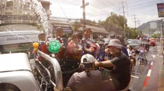 Children in pickup blast strangers with water cannons at Songkran festival Stock Footage