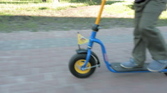 Child rides push kick scooter fast in summer park Stock Footage