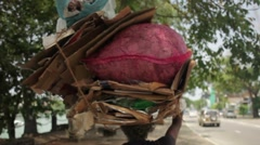 A day in the life of Sri Lanka - man carrying rubbish on his head Stock Footage