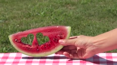 Female hand put a decorated watermelon slice with heart shaped holes on table Stock Footage