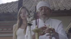 Balinese priest praying ceremony with young caucasian woman in temple, ungraded Stock Footage
