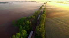 Freight train rolls across peaceful, foggy landscape at sunrise Stock Footage