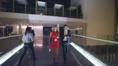 4K Business people working late, talking as they walk in large modern building - stock footage