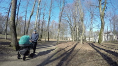father man push blue baby carriage in spring park tree alley. 4K - stock footage