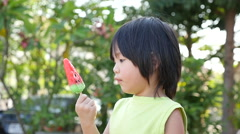 Cute Asian child eating an ice cream outdoors - stock footage