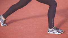 Fit teen girl wearing black sportswear in a red gym space doing long lunge Stock Footage