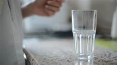 Woman pouring milk in a glass in the kitchen, closeup Stock Footage
