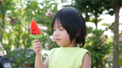 Cute Asian child eating an ice cream outdoors Stock Footage