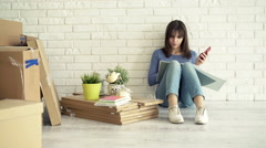 Young woman calculating bills on smartphone sitting on floor at her new home Stock Footage