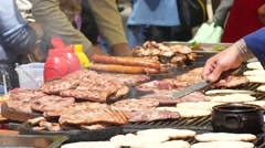 Street food festival of grilled meat  - cooking selling buying tasty meat dishes Stock Footage