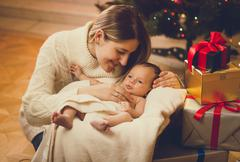 mother kissing baby boy lying in living room decorated for Christmas - stock photo