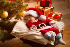Baby Santa sleeping under Christmas tree with presents Stock Photos