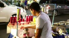 Asian man at brightly lit fruit juice street vendor cart Stock Footage