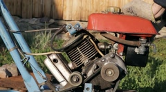 Walk-behind tractor in a village Stock Footage