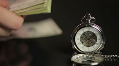 Closeup of silver pocket watch, hands counting paper money, time flies fast Stock Footage