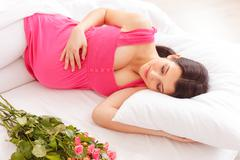 Pretty expectant mother is sleeping near flowers - stock photo