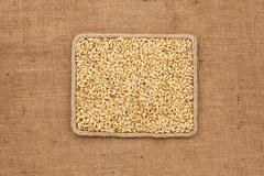 Frame made of rope with barley grains on sackcloth, view from above - stock photo