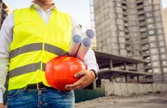 toned photo of foreman holding helmet and blueprints - stock photo