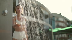 Beautiful woman in swimming costume taking a shower outdoors slow motion Stock Footage