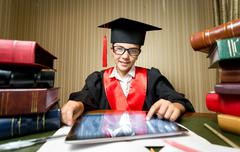 smiling girl in graduation cap using digital tablet at library - stock photo