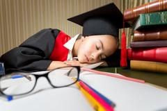 Portrait of tired girl in graduation cap seeping at library - stock photo